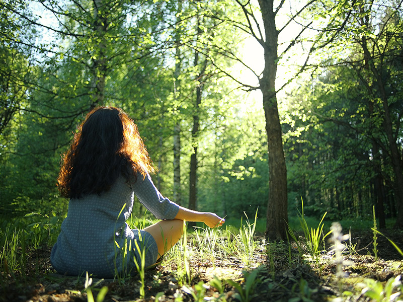 woman sitting in a forest clearing. © Kichigin/shutterstock
